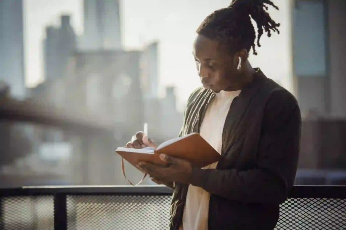 young writer taking notes in diary while standing on terrace
