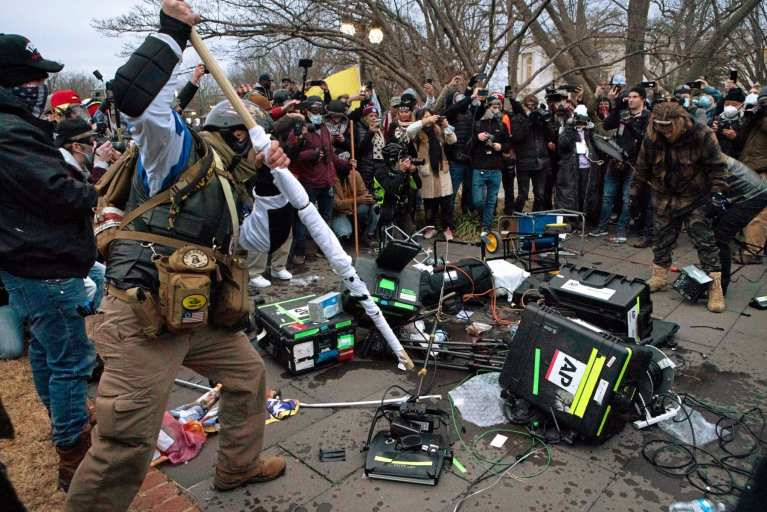 Insurrectionists destroying media equipment during the siege of the Capitol, January 6, 2021
