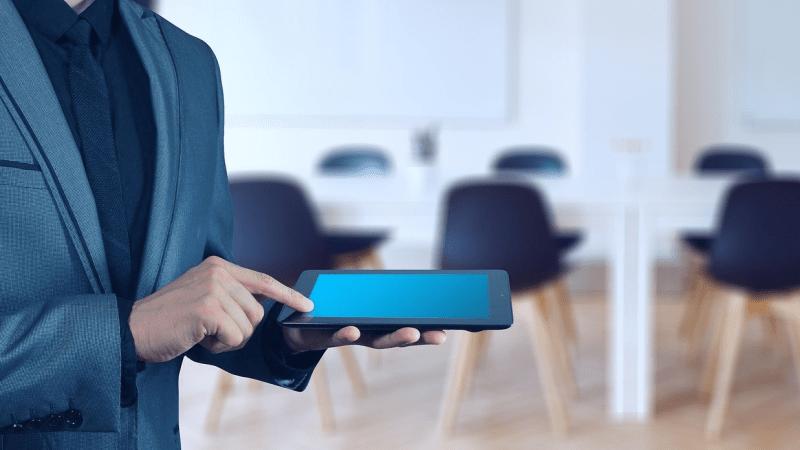 Homem de terno com tablet na mão e sala de reunião de fundo