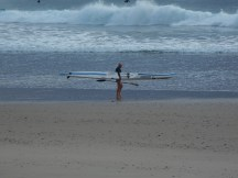 The perfect example of why exercise counts. Older guy looking fit and invigorated heading out for a surf just after dawn at Coffs Harbour beach.