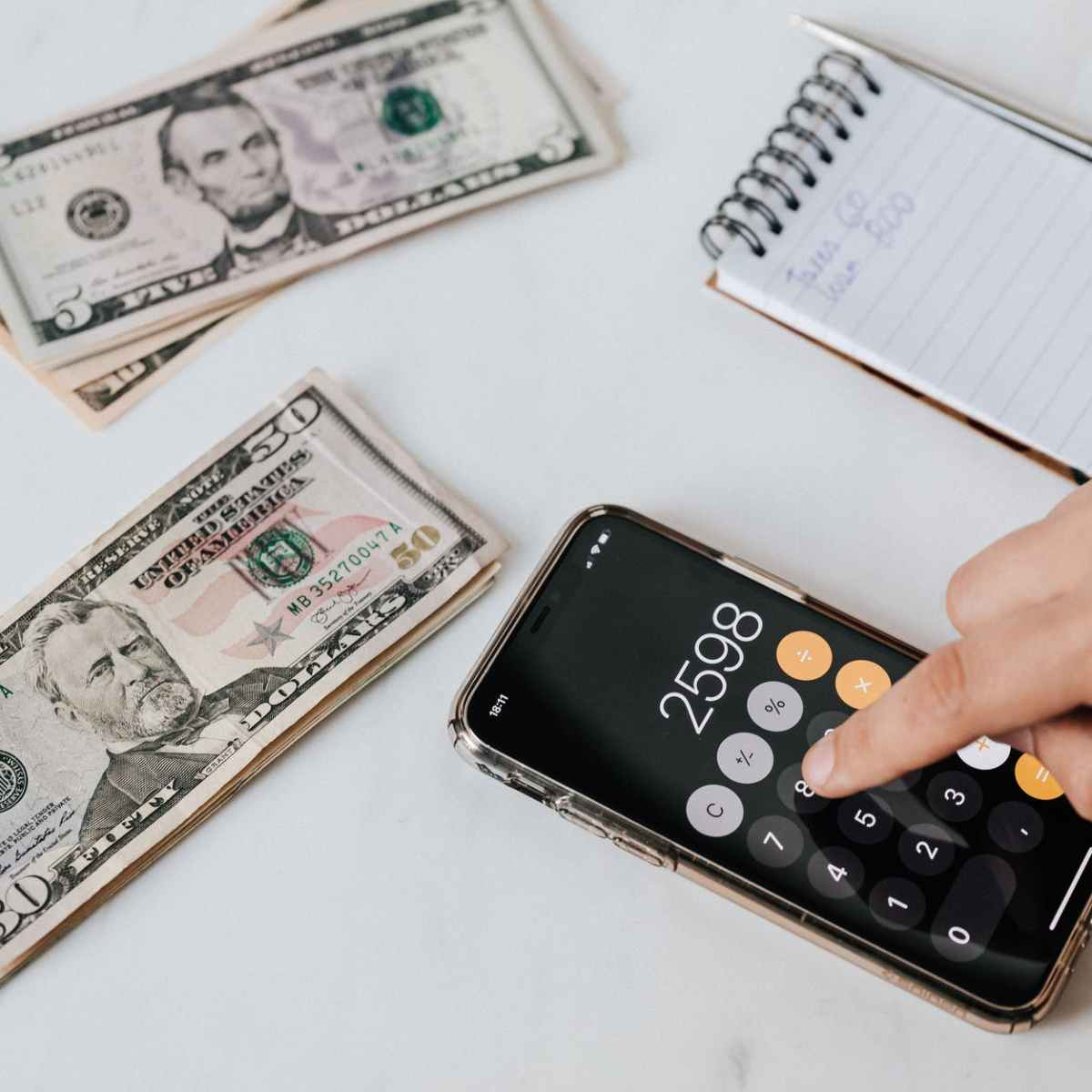 crop unrecognizable financier using calculator on smartphone near dollar banknotes