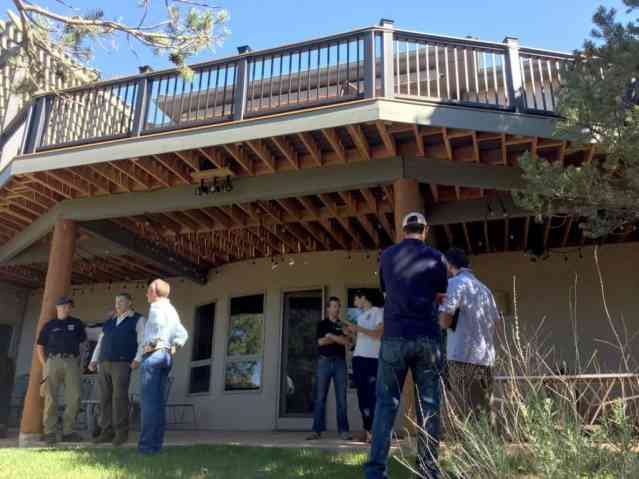 Participants inspecting a wooden deck; such inspections can be a critical component of home wildfire evaluations