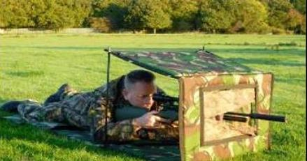 Man aiming an air rifle through a small camouflage hide