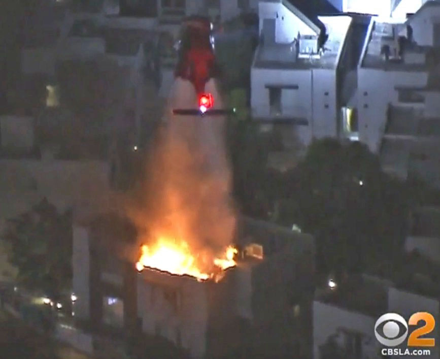 Night flying helicopter drops water on structure fire near World Series game