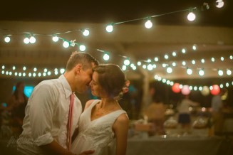 the bride and groom share a kiss under the twinkling lights