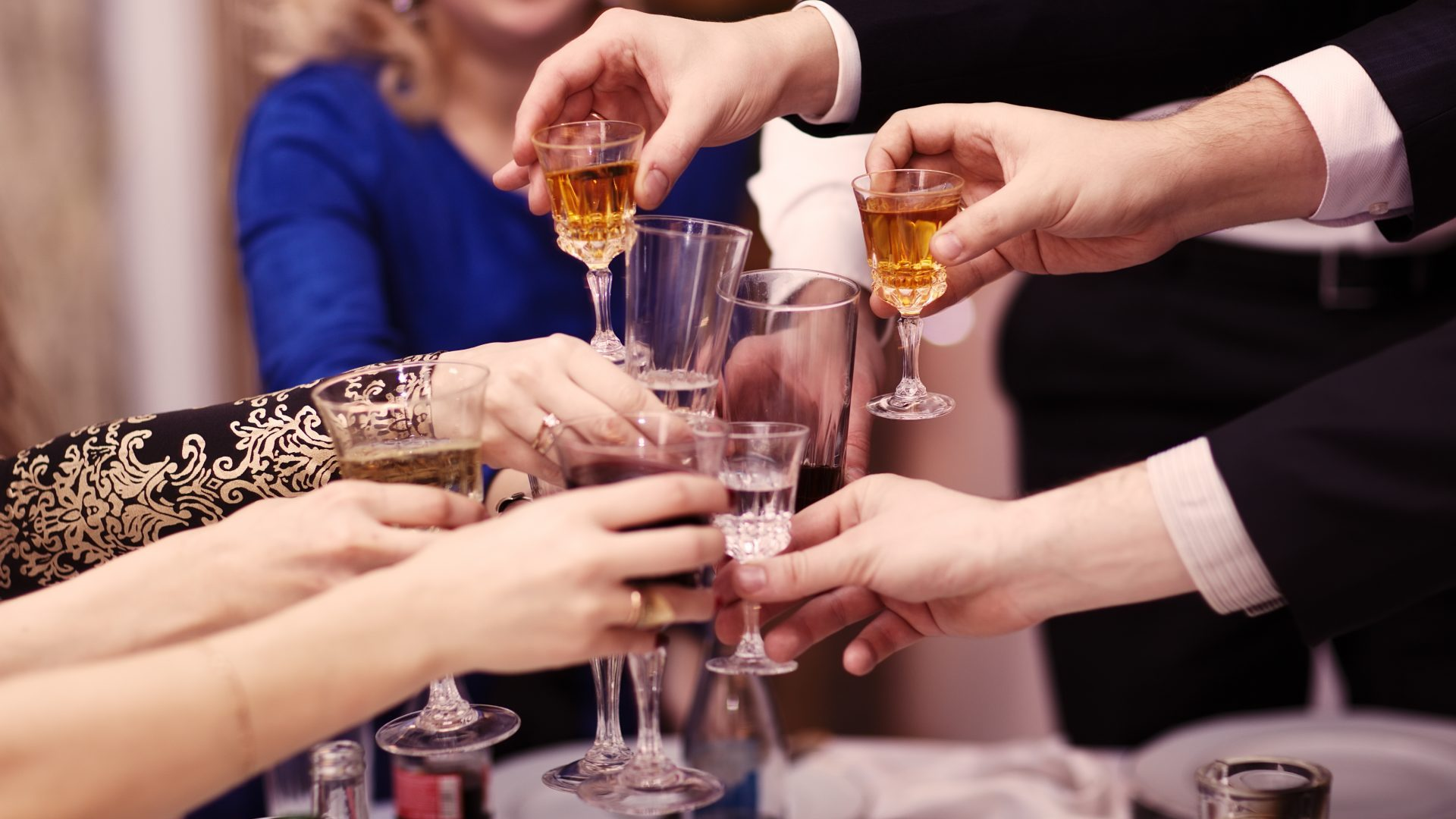 Group of people toasting at a celebration clinking their glasses together in congratulations , close up view of their hands