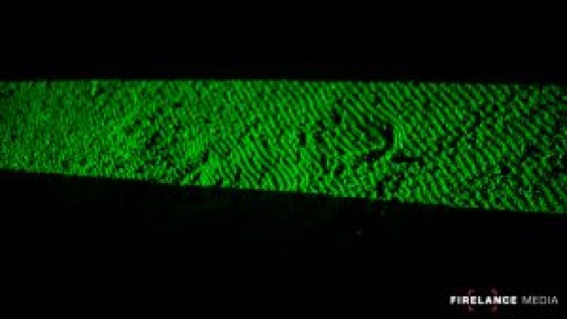 Green laser highlighting a footprint during night tracking