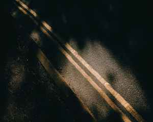 asphalt road with marking lines near soil and shadows