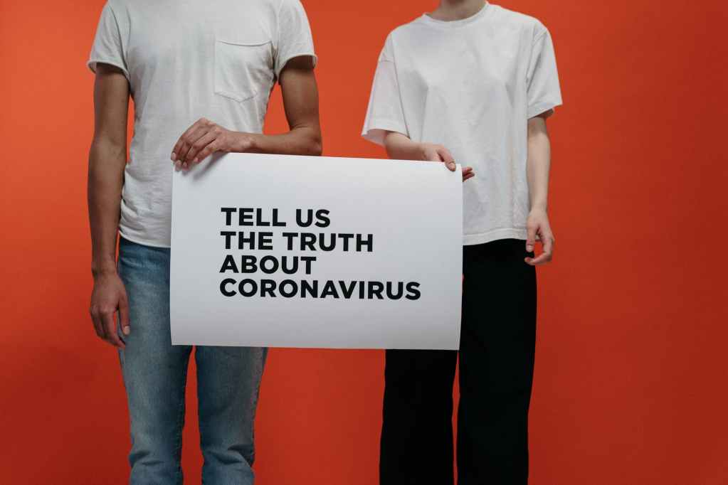 people holding a poster asking about facts on coronavirus