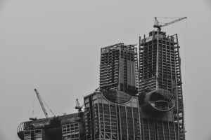 grayscale photography of high rise building with tower cranes