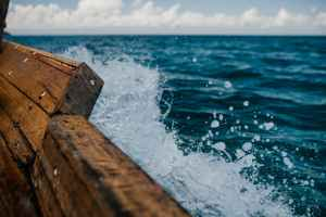 part of wooden boat floating in sea