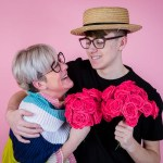 mum and son against a pink background holding flowers for a website video