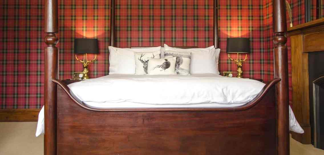 Four poster bed and cast iron fireplace in the Findhorn room at Firhall Highland B&B