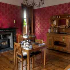 The dining room at Firhall highland bed and breakfast with tables laid up for two people and a wood burning stove with a wood pile next to it