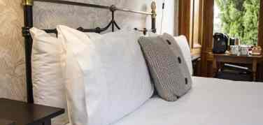 Crisp white pillow cases on a kingsize bed with a coffee machine in the background and a chunky knit cushion