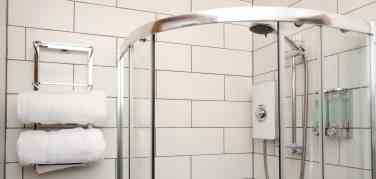 White tiled bathroom with corner circular shower and white fluffy towels