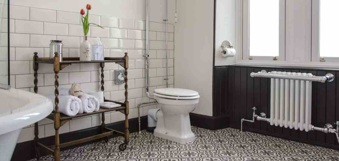 bathroom with old fashioned wall mounted radiator and toilet with high cistern and black and white floor tiles