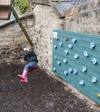 child on a button swing next to climbing wall