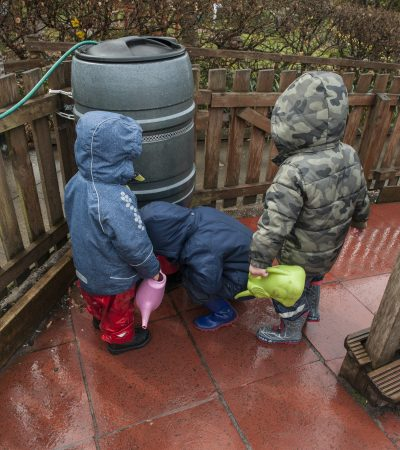 children getting water from water barrel
