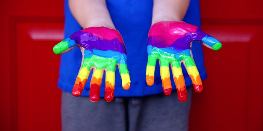 Open hands painted with rainbows