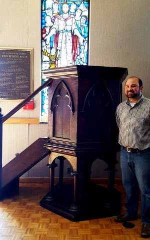 Mr. Matthew Kilgore stands beside the pulpit he has loaned to the World Methodist Museum.