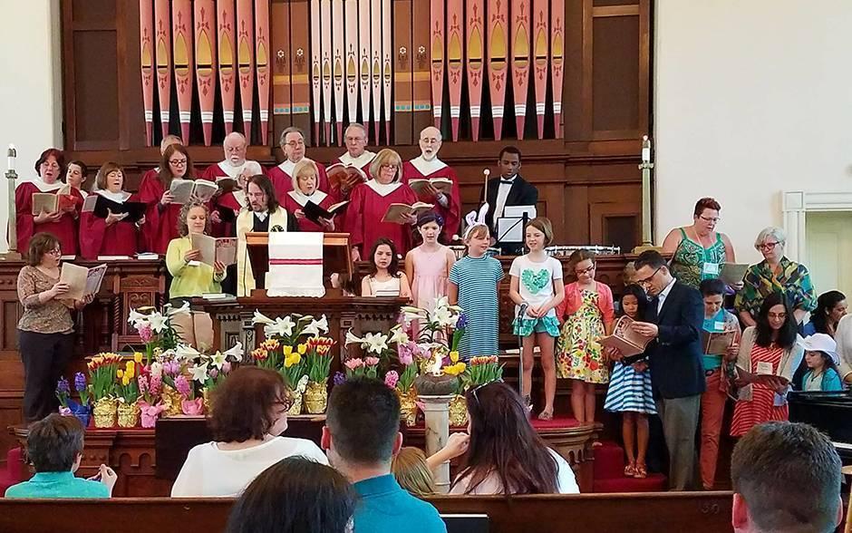 A choir and church members sing at First Parish