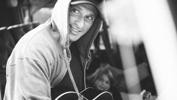 Dan Bern wearing a hoody and playing guitar