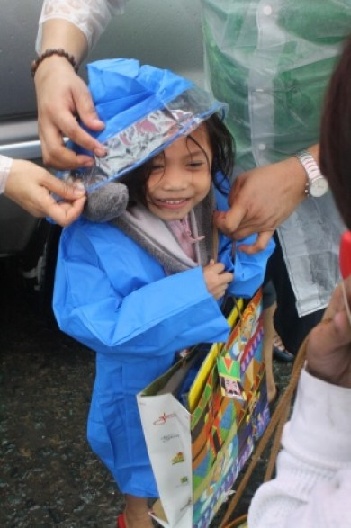 A child excitedly wore her raincoat as volunteers assisted her.