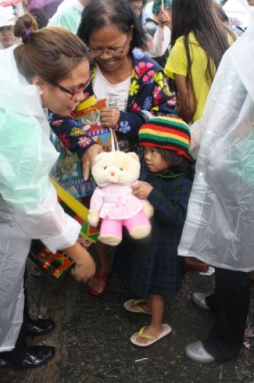 A kid received a stuffed toy donated by a child in Manila.