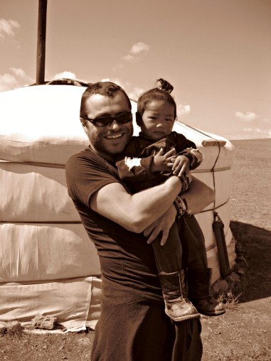 Paul poses with a child in Mongolia.