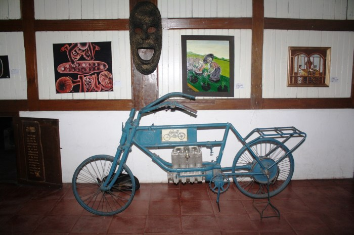 The motorized bicycle parked at the back of the house.