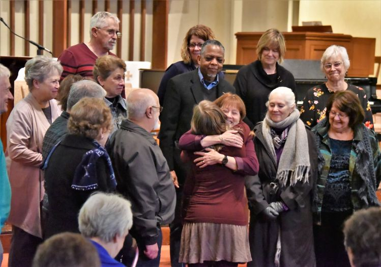 People hugging surrounded by church family