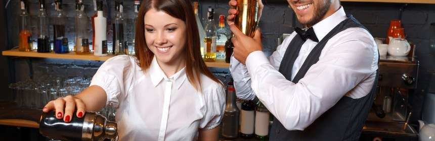 Portrait of a waitress wearing a white blouse pouring a cocktail from a shaker smiling and a handsome bartender mixing a drink and watching her, shelves full of bottles with alcohol on the background