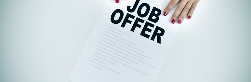 high-angle shot of the hands of a businesswoman with a document with the text job offer at an office desk