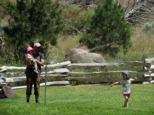 père et enfants jouant devant un jet d'eau