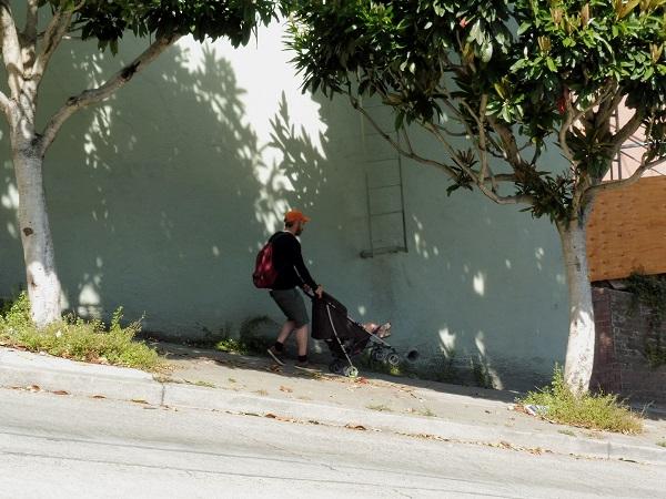 papa tenant une poussette dans une pente raide dans San Francico