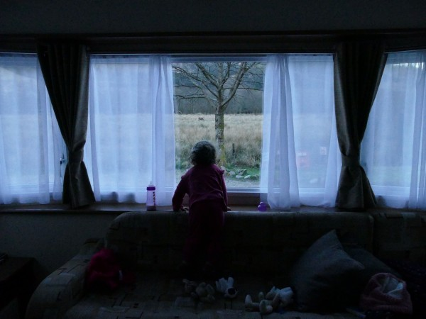 enfant à la fenêtre dans un mobil-home dans le Glen Coe (Ecosse)