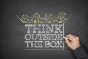 """A chalkboard drawing with light bulbs overflowing out of a box that says """"Think outside the box."""" For optimizing email campaigns"""