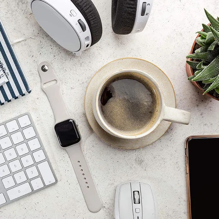 A white desktop with a keyboard, coffee, a watch and other office supplies