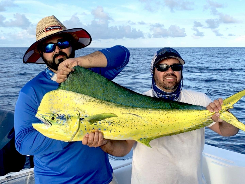 Two men holding a big Mahi Mahi on a boat