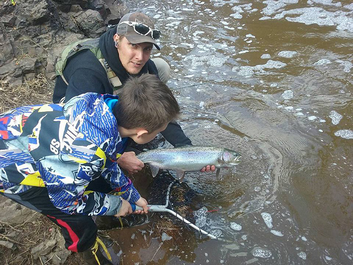 A fishing guide and a young boy catching fish.