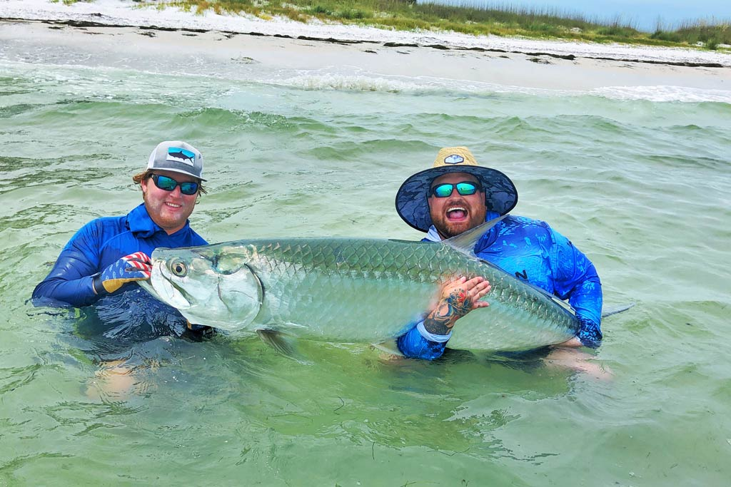 Two smiling men in caps and sunglasses standing in water with a Tarpon in their hands