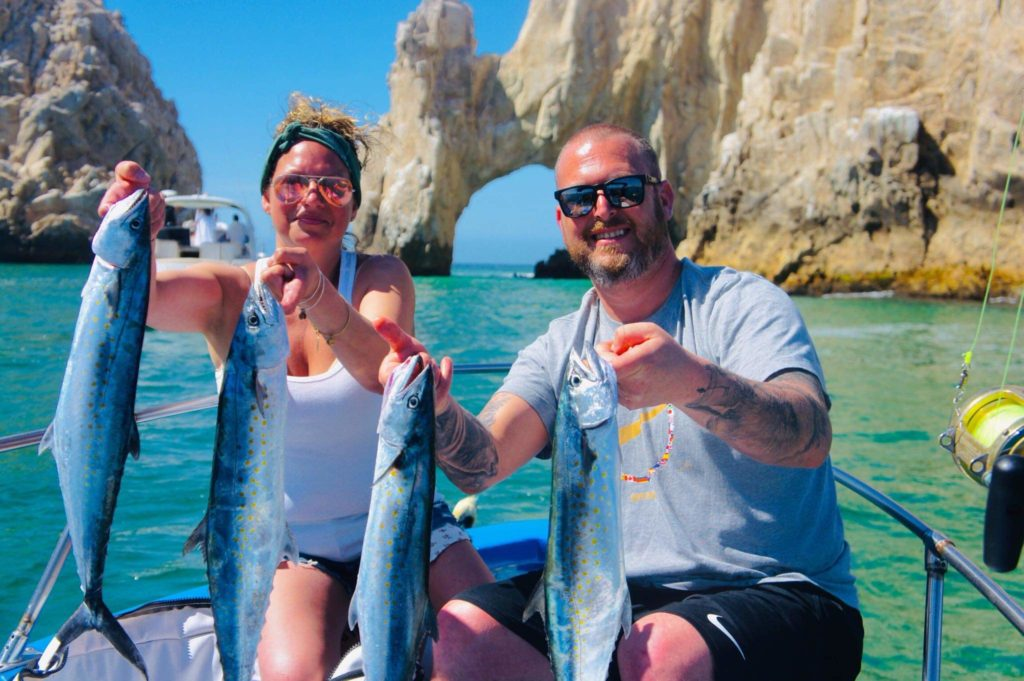 a husband and wife posing on a fishing boat in Cabo San Lucas, each holding two mackerel fish in their hands
