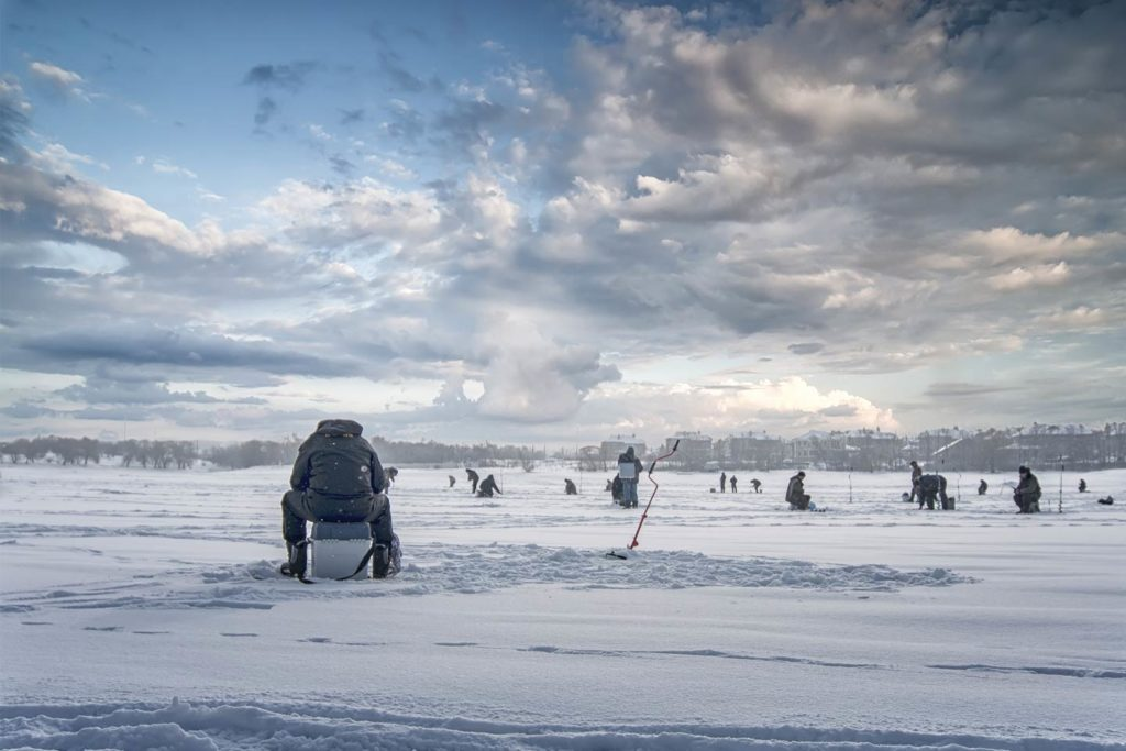 Multiple anglers set up for ice fishing.