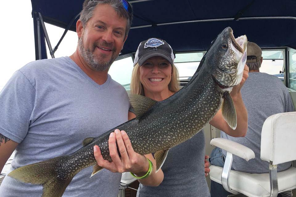 A happy couple holding a Lake Trout caught on Lake Superior.