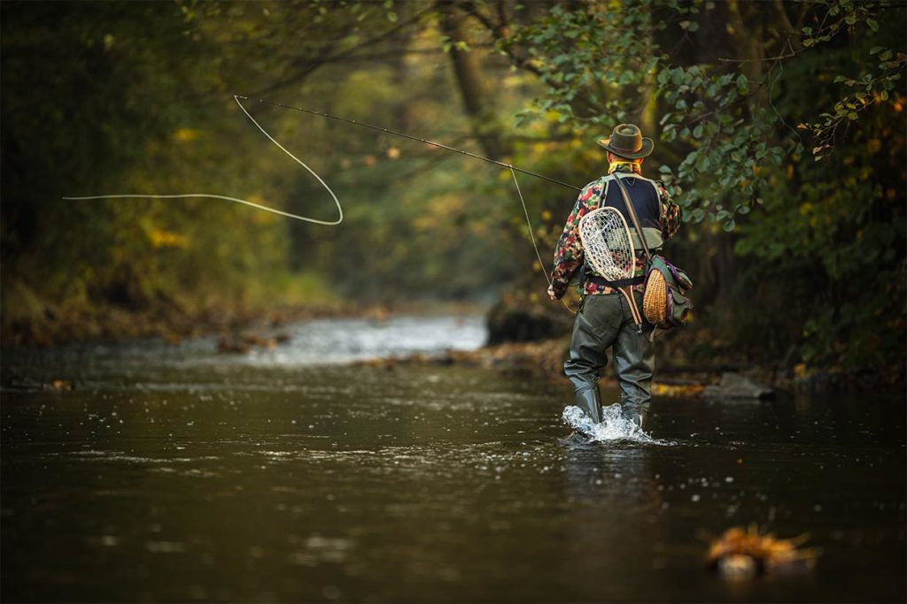 A man casts his fly line in the wilderness in South Carolina