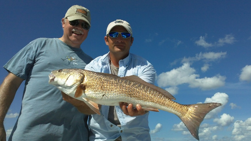 Captain Brian David holding a fish next to a smiling client