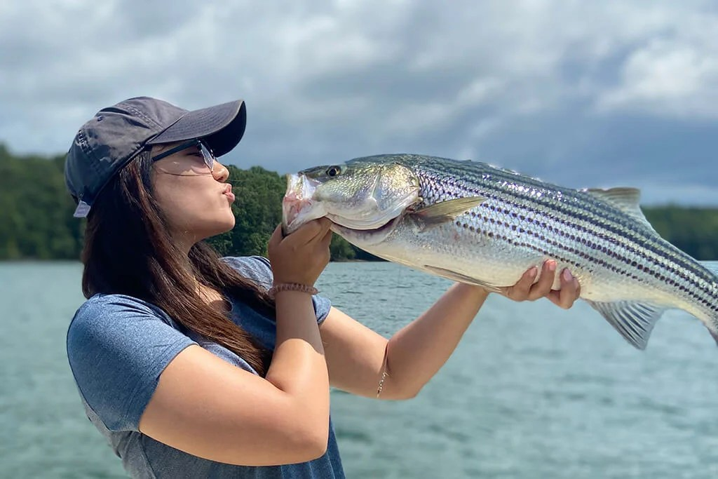 A young woman holding a Striped Bass up in front of her