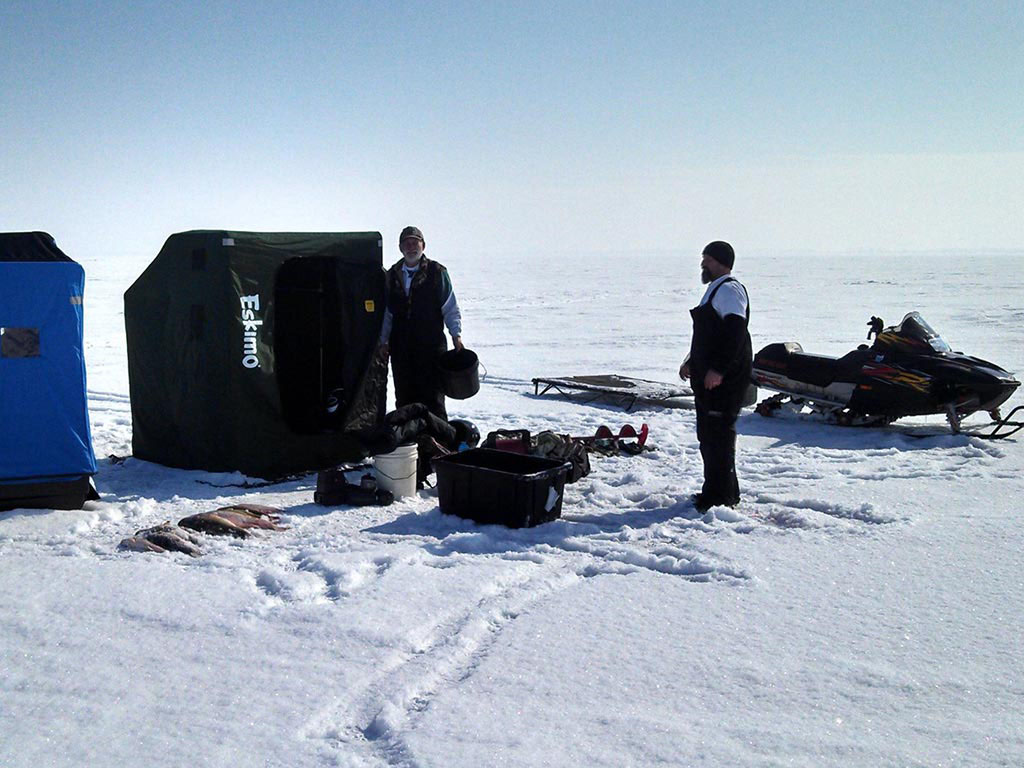 Two ice fishermen standing next to their gear and the fish they caught.