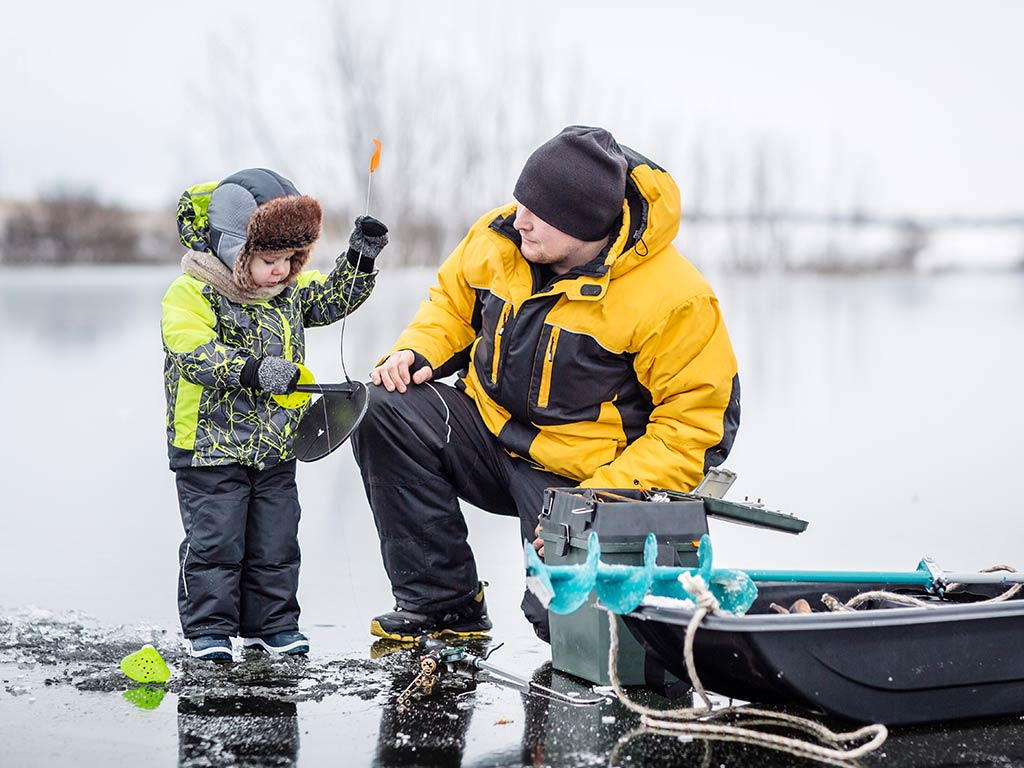 A father and son standing over a hole in the ice while setting up their ice fishing equipment.